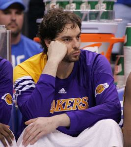 Pau Gasol in long sleeve Lakers warm-ups sits on the bench watching